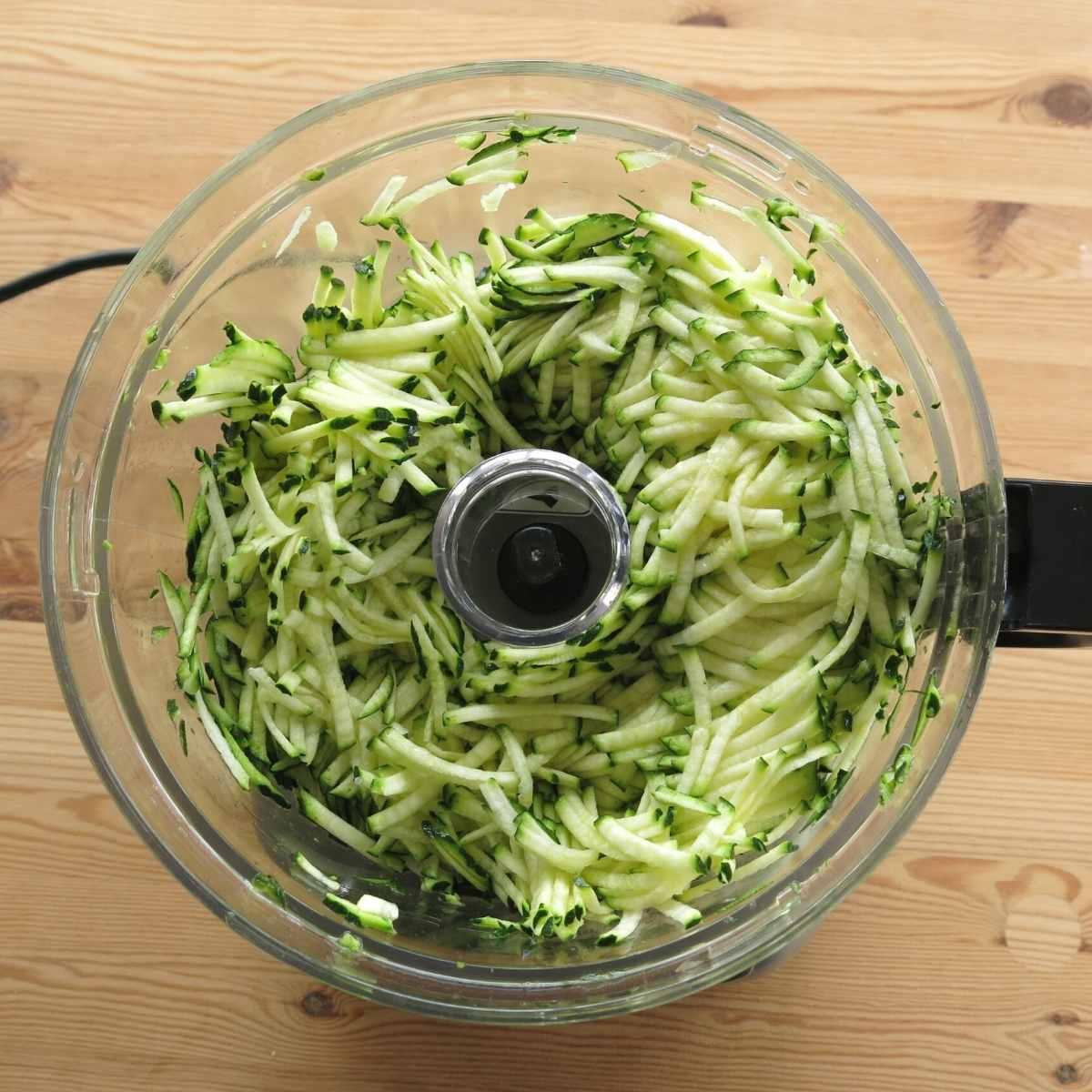 Shredded zucchini in food processor bowl.